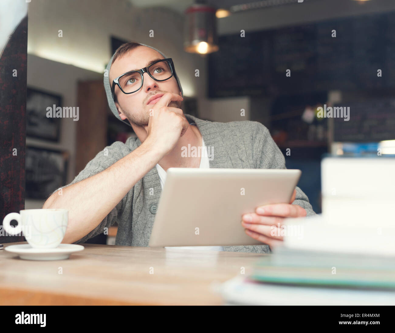Dreaming man using digital tablet at cafe. Krakow, Poland - Stock Image