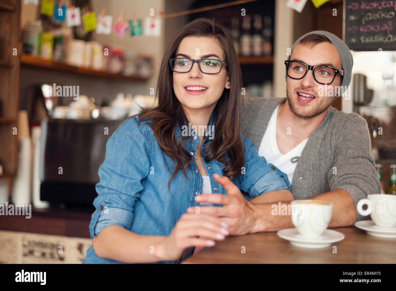 Hipster couple talking with friends at cafe. Krakow, Poland - Stock Image