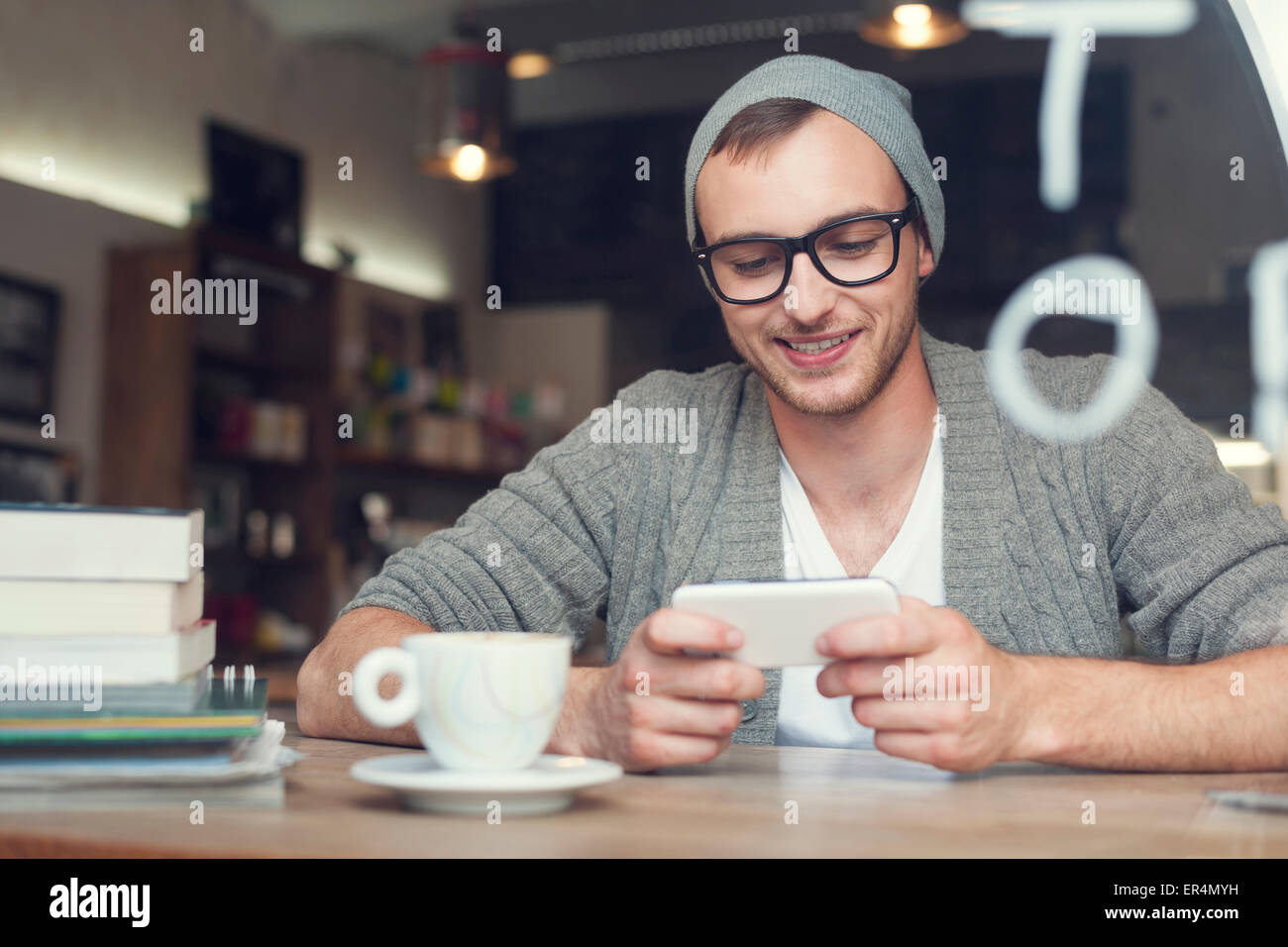 Hipster man with mobile phone at cafe. Krakow, Poland - Stock Image