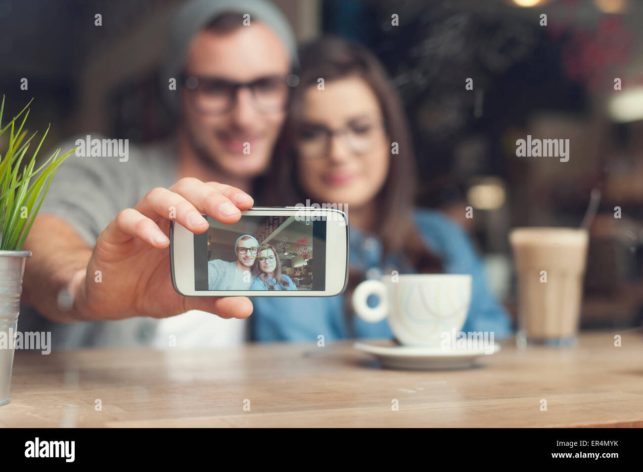 Hipster couple taking selfie at cafe. Krakow, Poland - Stock Image