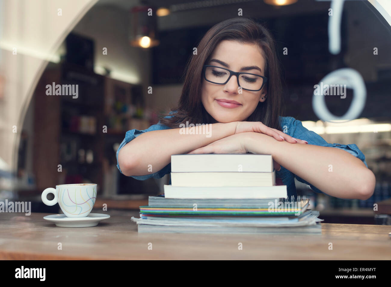 Beautiful and smiling female student at cafe. Krakow, Poland - Stock Image
