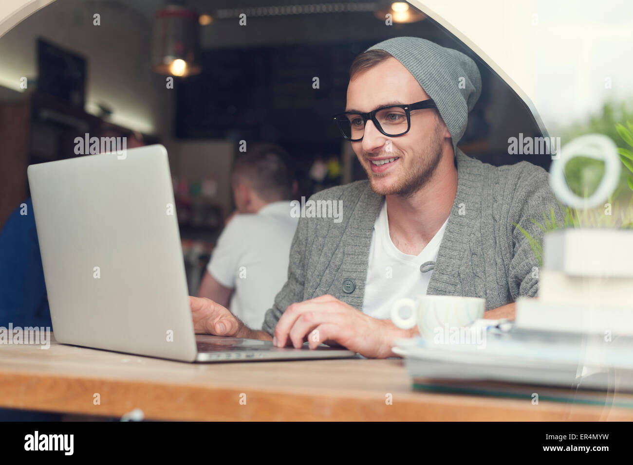Handsome hipster using laptop at cafe. Krakow, Poland - Stock Image