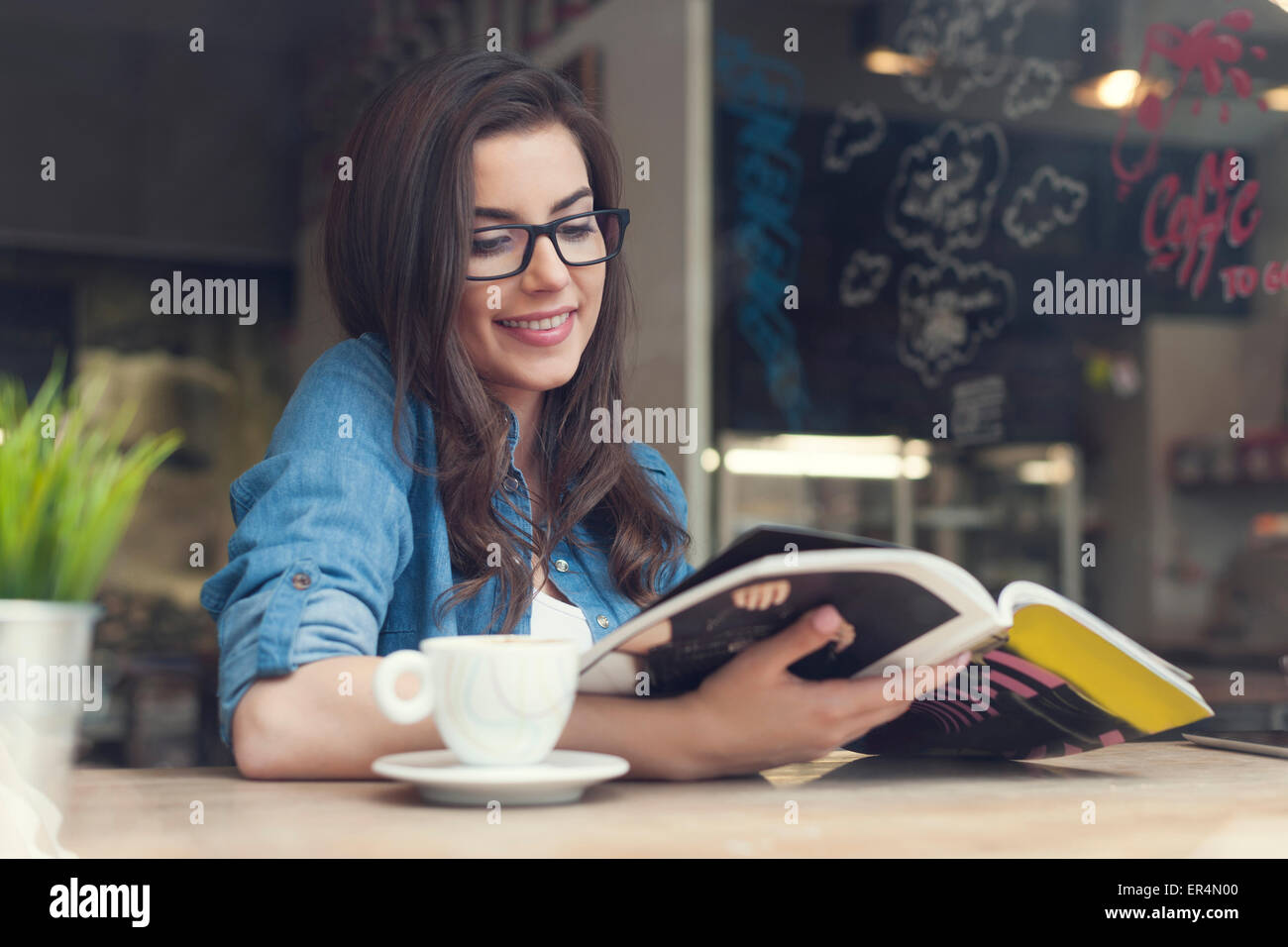 Smiling woman reading newspaper at cafe. Krakow, Poland - Stock Image