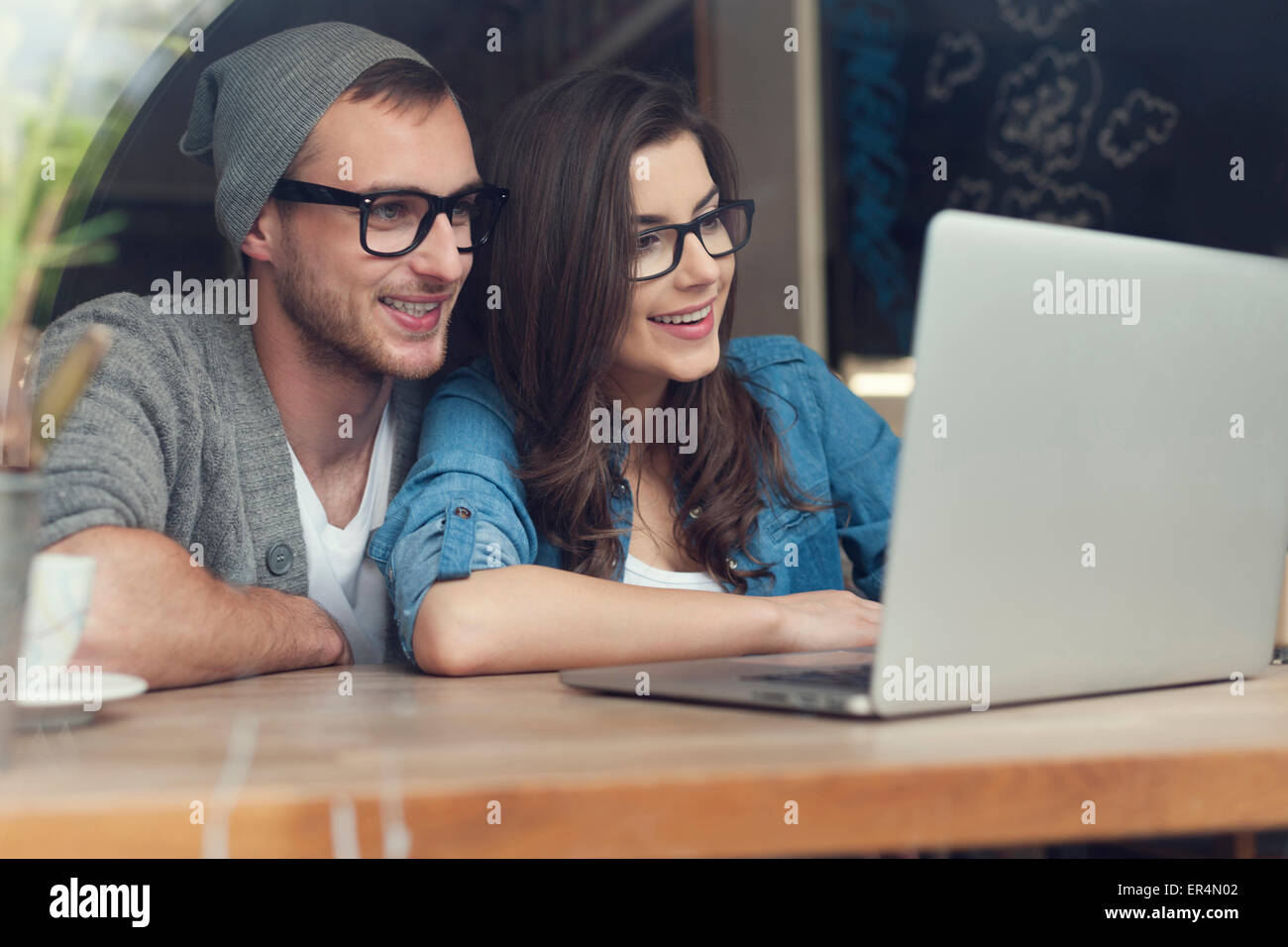 Stylish couple with contemporary laptop in cafe. Krakow, Poland - Stock Image