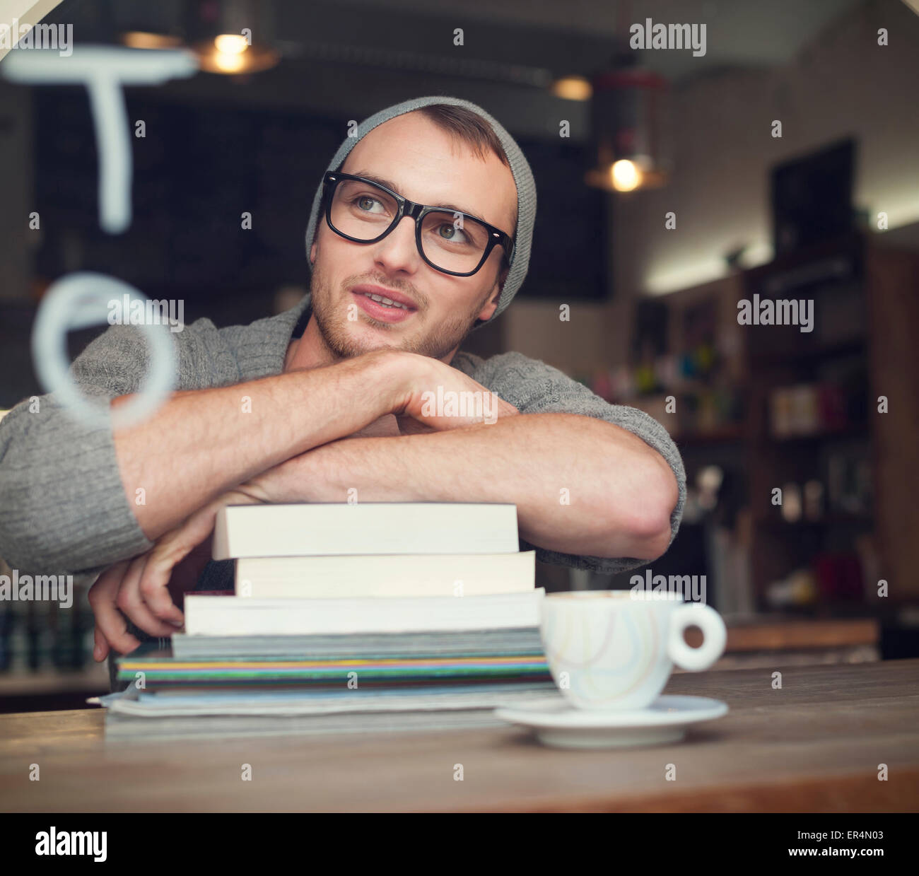 Dreaming nerdy male student in cafe. Krakow, Poland - Stock Image