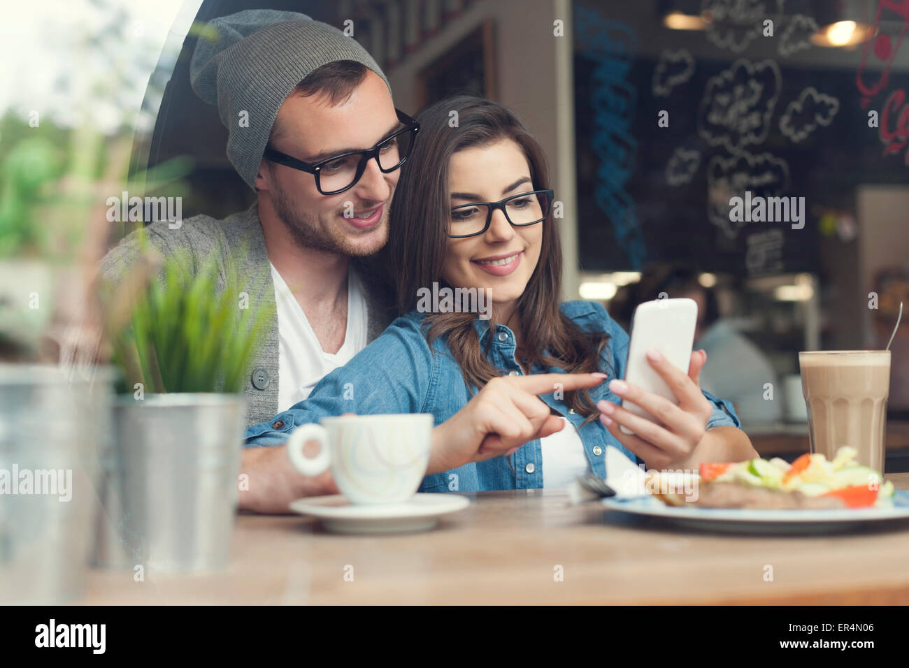 Embracing couple using mobile phone in cafe. Krakow, Poland - Stock Image
