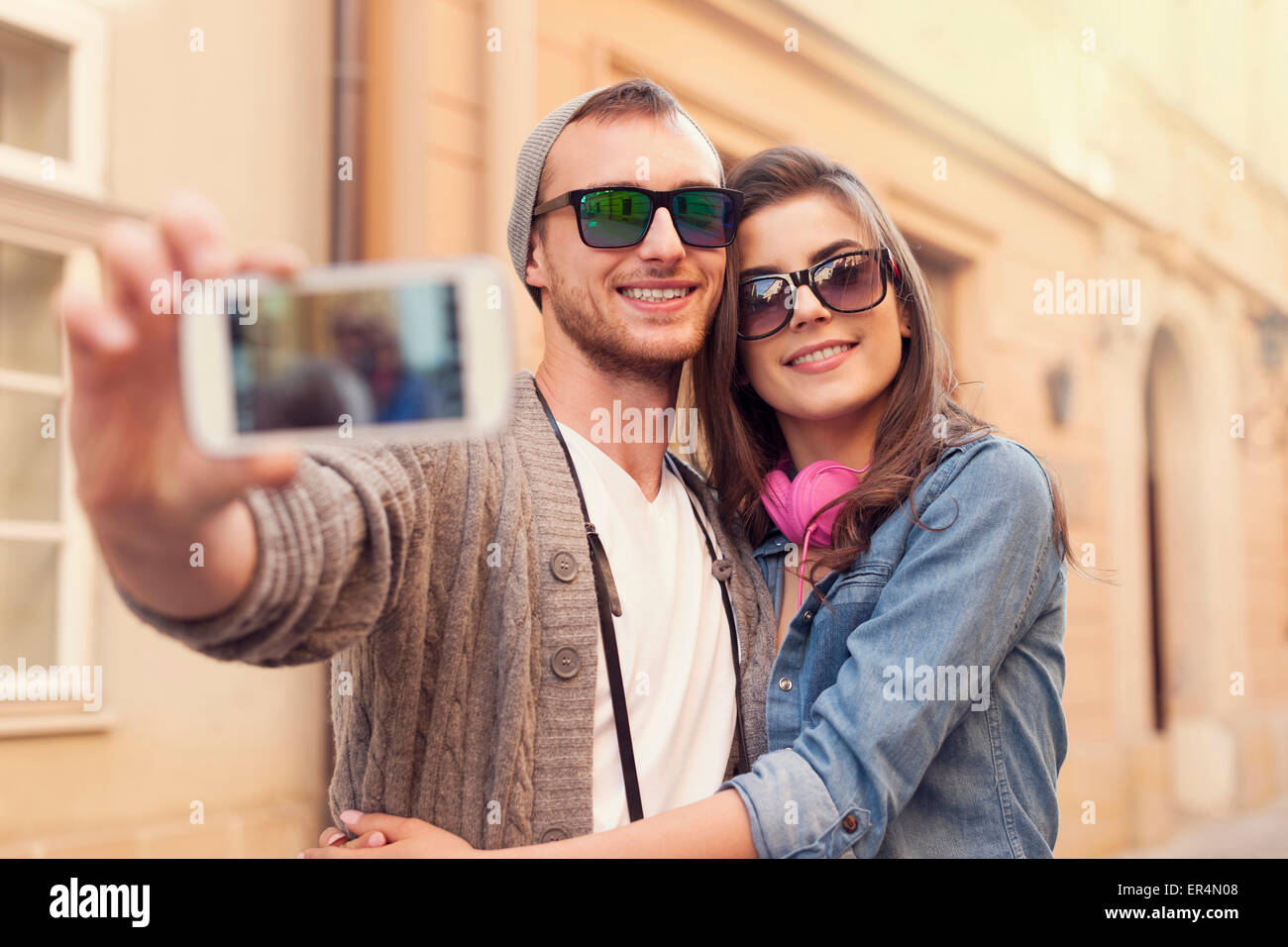 Fashionable couple taking selfie by mobile phone. Krakow, Poland Stock Photo