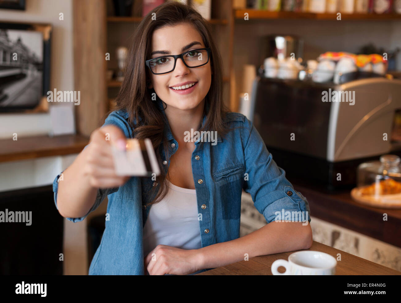 Smiling woman paying for coffee by credit card. Krakow, Poland - Stock Image
