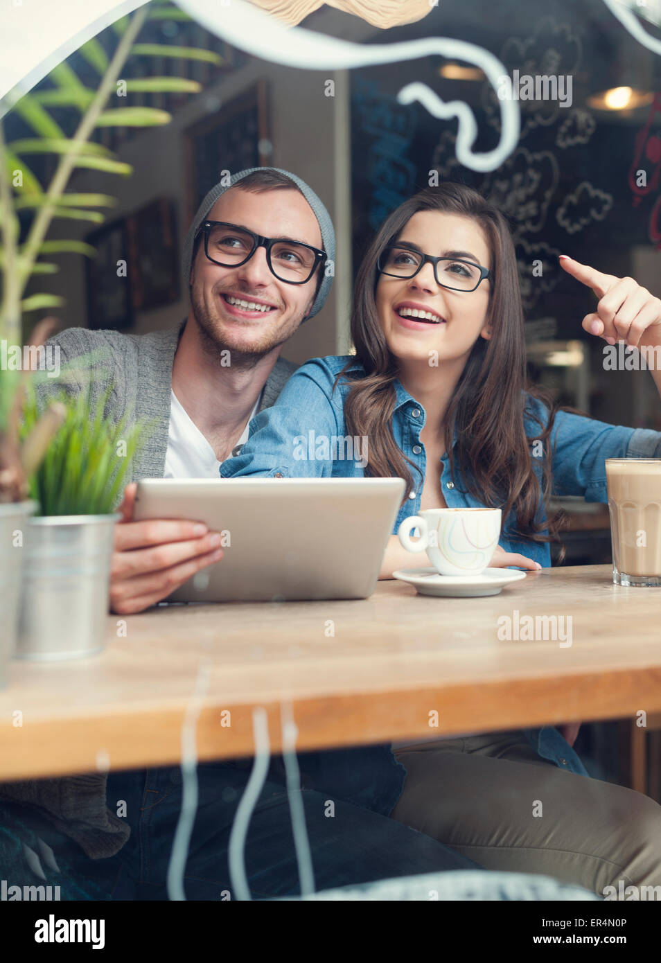 Happy couple using digital tablet at cafe. Krakow, Poland - Stock Image