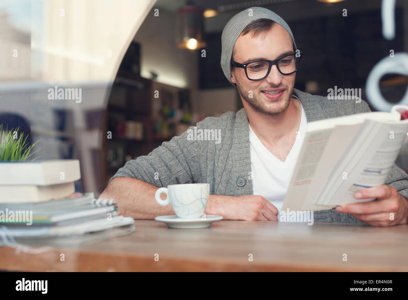 Smiling hipster man reading book at cafe. Krakow, Poland - Stock Image