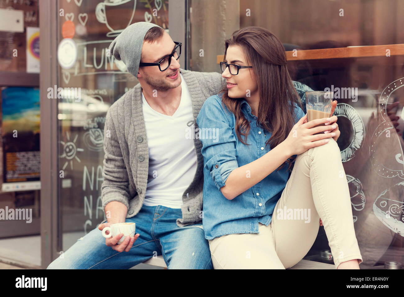 Young people relaxing with cup of coffee outside the cafe. Krakow, Poland - Stock Image
