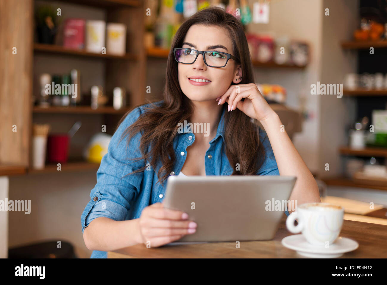 Thoughtful young woman using digital tablet at cafe. Krakow, Poland - Stock Image