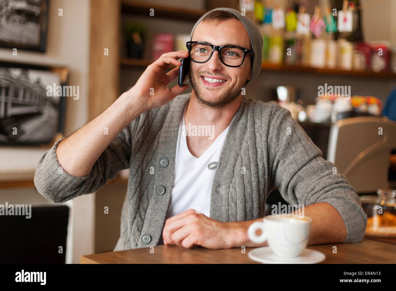 Hipster man talking by mobile phone at cafe. Krakow, Poland - Stock Image