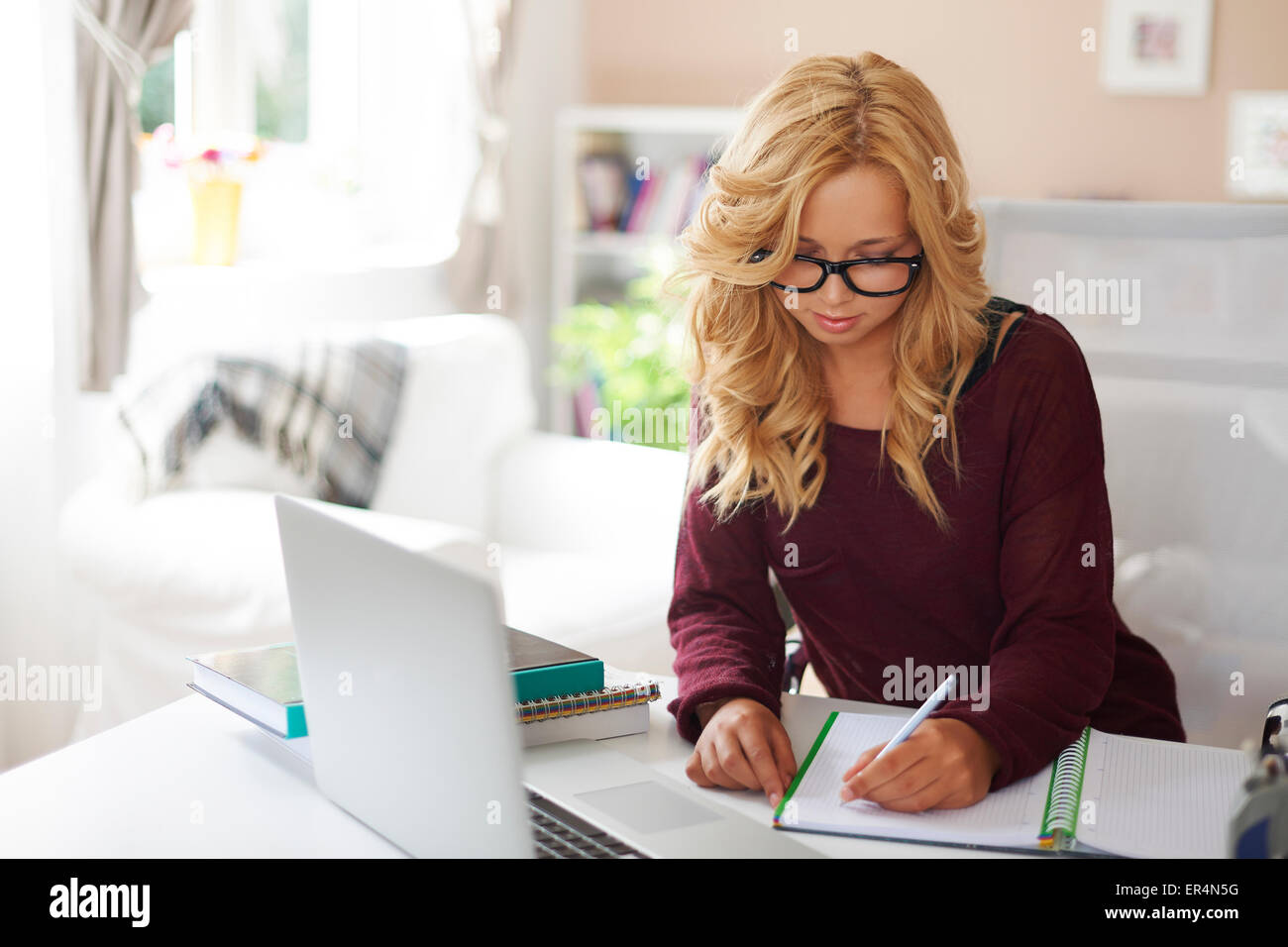 Blonde young girl doing homework after school. Debica, Poland - Stock Image