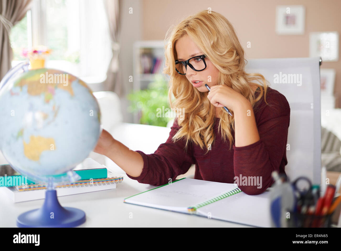 Focus girl studying globe of earth at home. Debica, Poland - Stock Image