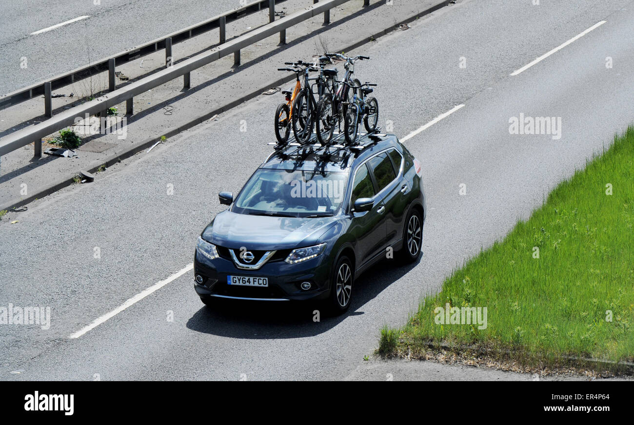 Nissan Qashqai car with roof rack full of bicycles on holiday trip on road - Stock Image