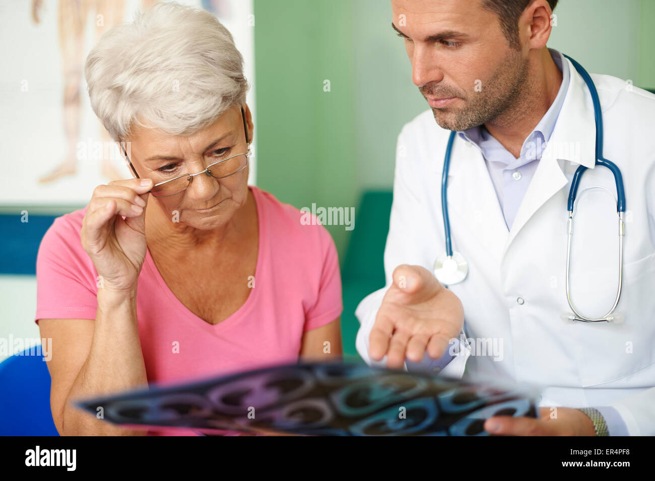 Doctor with his senior patient analyzing medical test. Debica, Poland - Stock Image