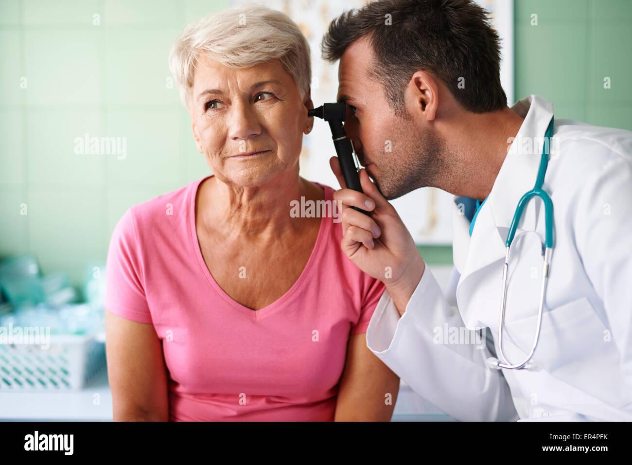 Doctor examining ear of senior woman. Debica, Poland Stock Photo