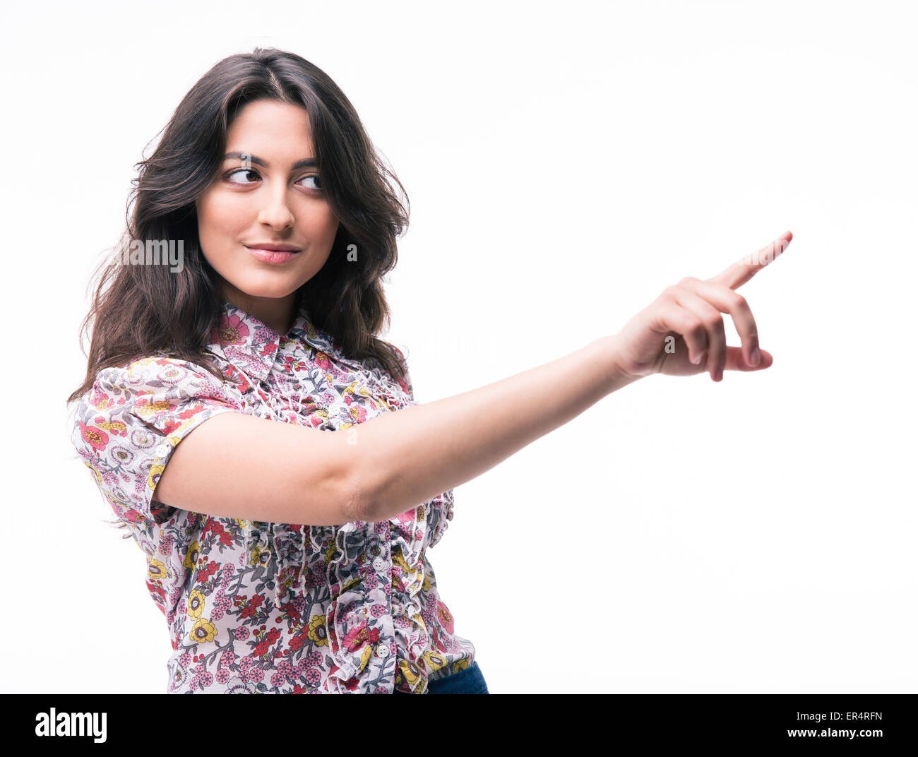 Cute woman pointing finger away isolated on a white background - Stock Image