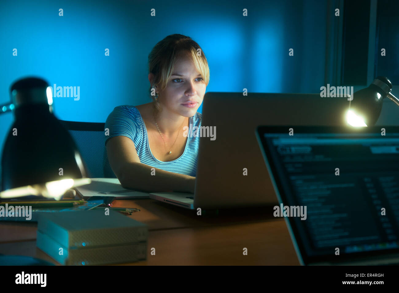 Beautiful woman working late at night in office, surfing the web and writing post on social network with laptop - Stock Image