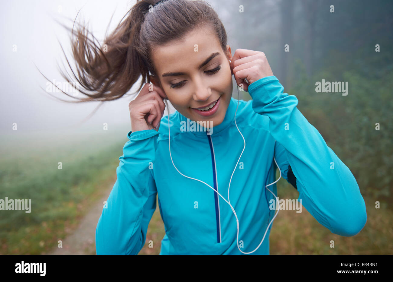 Running is the time to listen to her favourite sounds. Debica, Poland - Stock Image