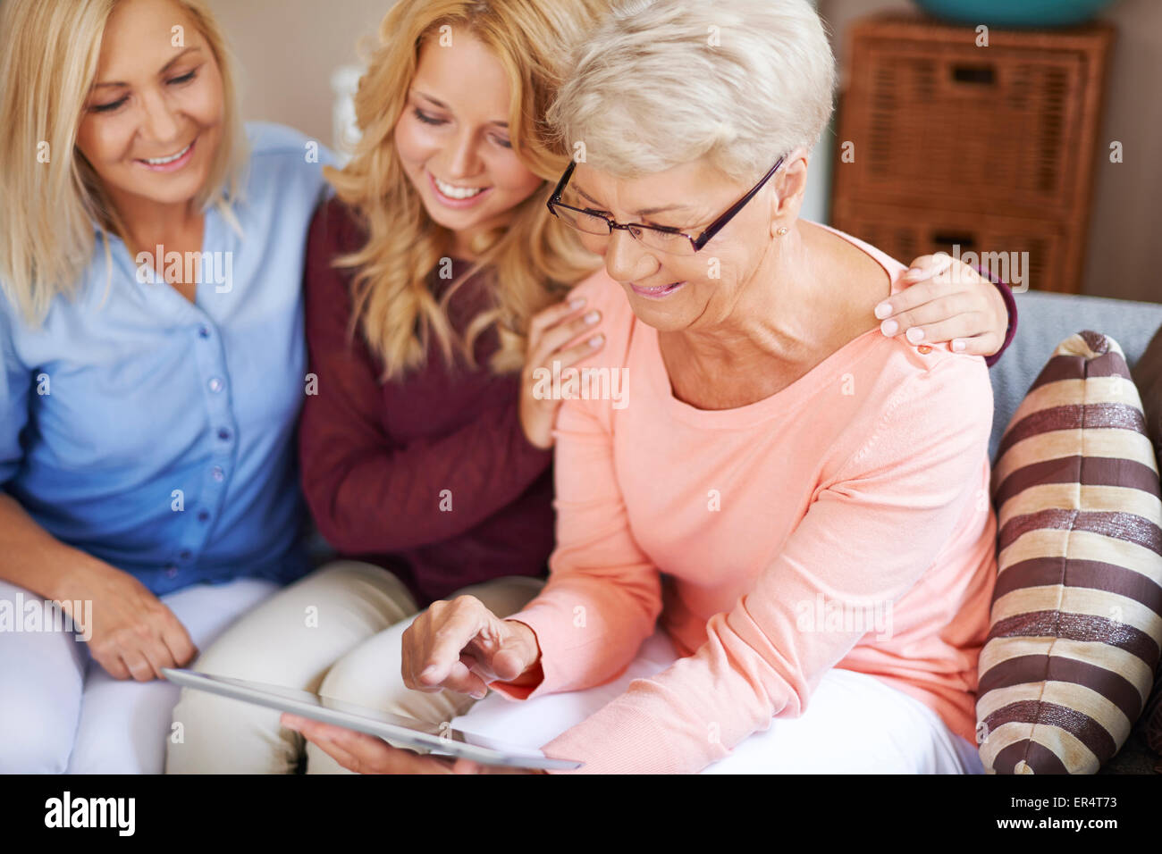 Girl with mom supporting grandma who is learning to use digital tablet. Debica, Poland - Stock Image
