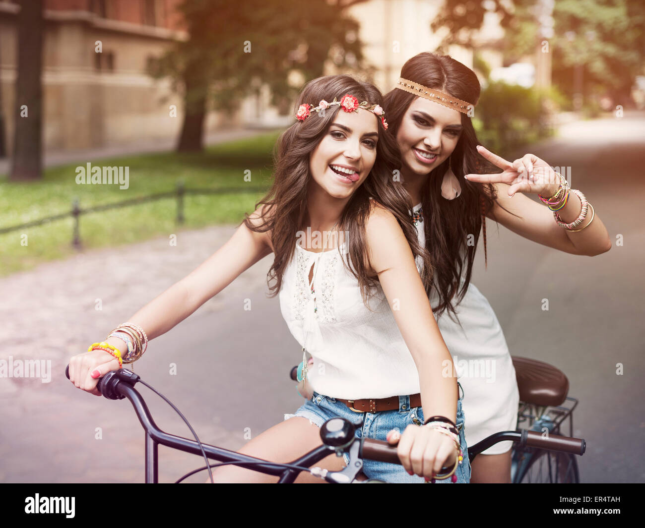 Portrait of funny boho girls on a tandem bicycle. Krakow, Poland - Stock Image