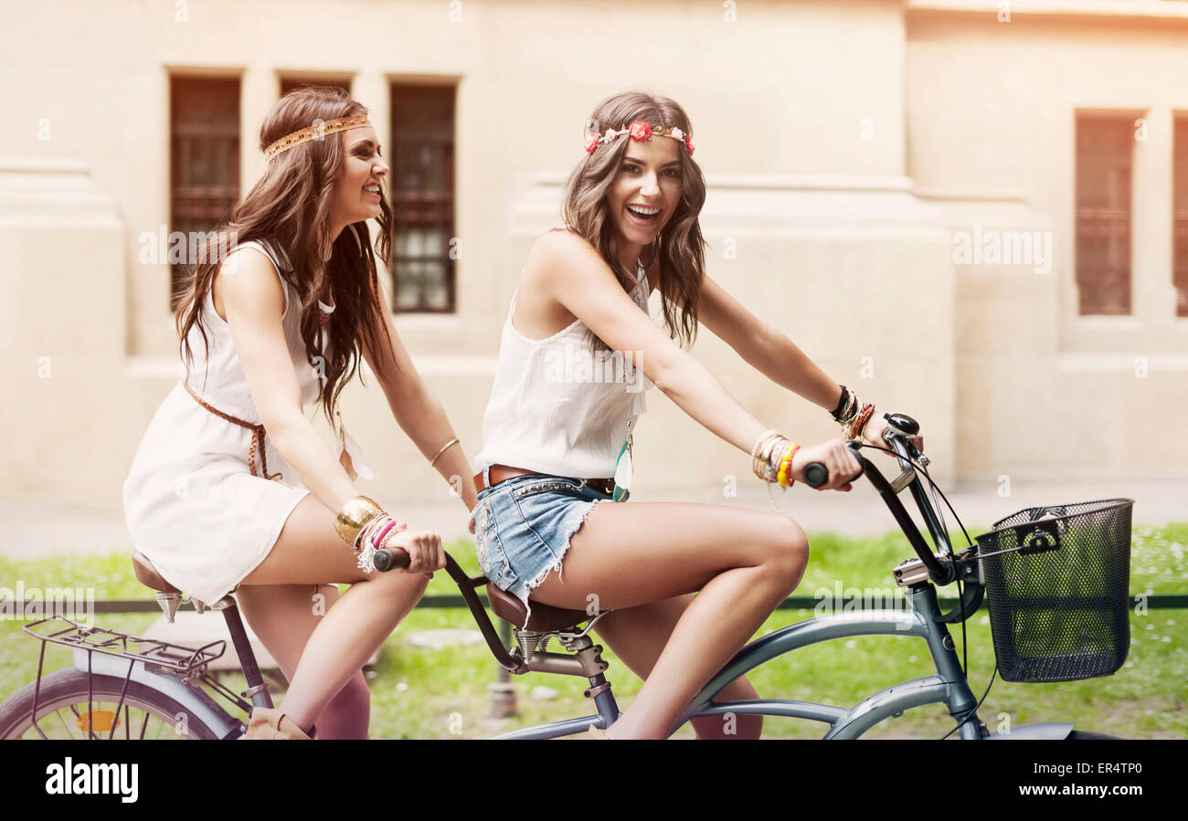 Happy hippie women have fun riding on a tandem. Krakow, Poland - Stock Image