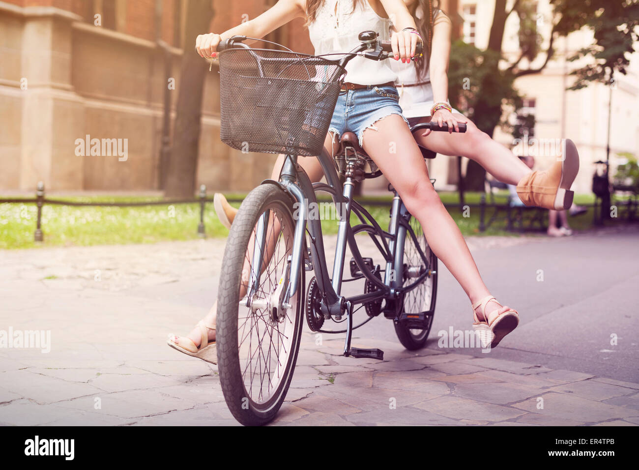 Part of boho girls legs during tandem bike ride. Krakow, Poland - Stock Image