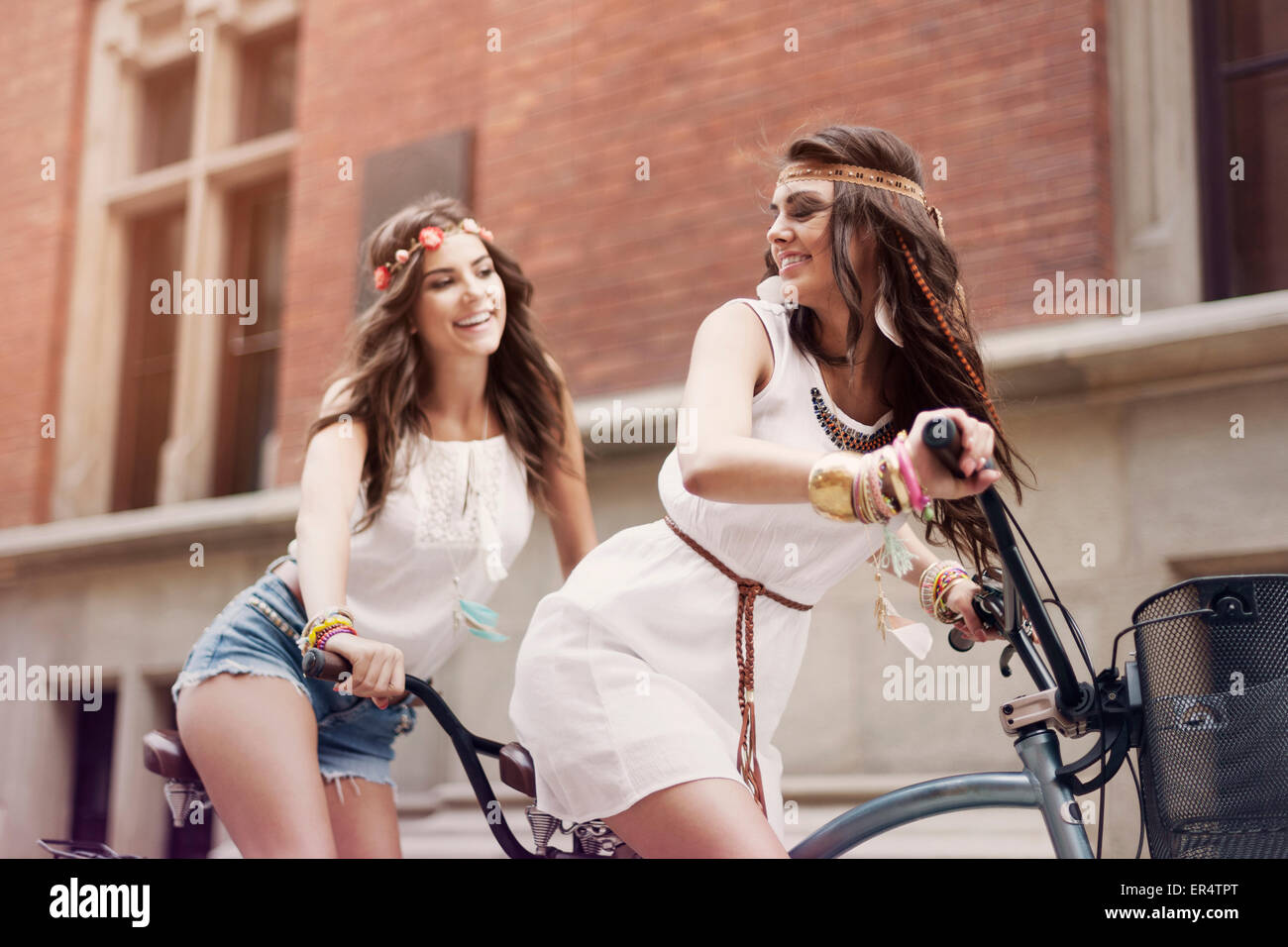 Retro portrait of two friends riding tandem bicycle. Krakow, Poland - Stock Image