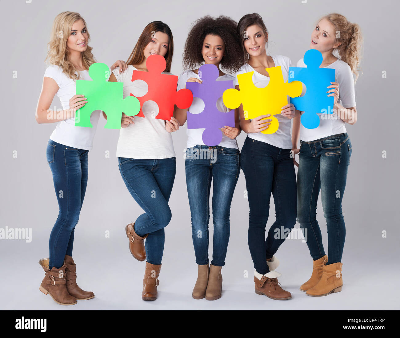 multi-ethnic girls with colored jigsaw puzzle. Debica, Poland - Stock Image