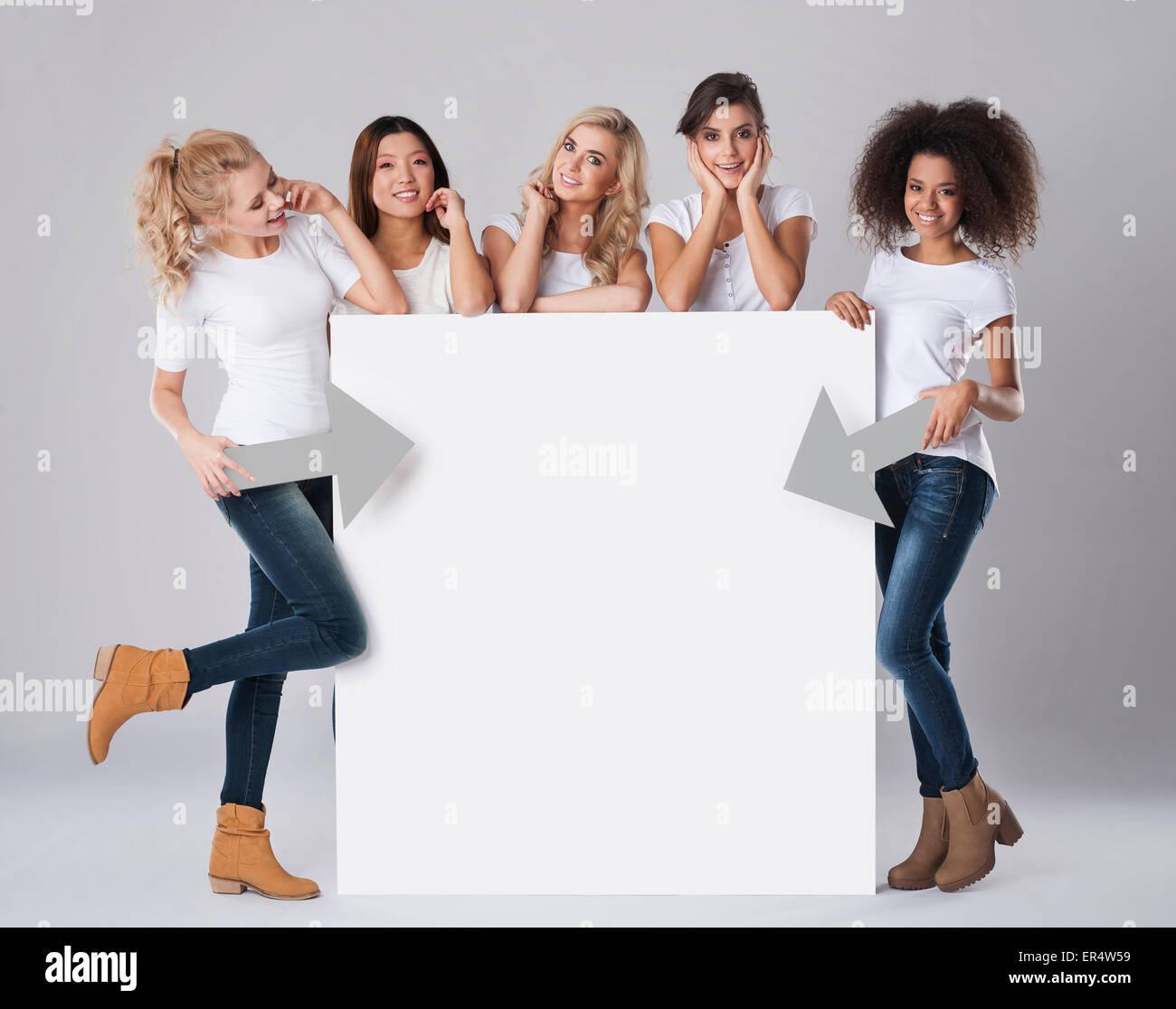 Multi-ethnic women with empty billboard. Debica, Poland - Stock Image
