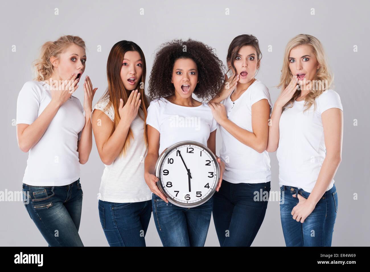 Multi-ethnic shocked women with clock. Debica, Poland - Stock Image