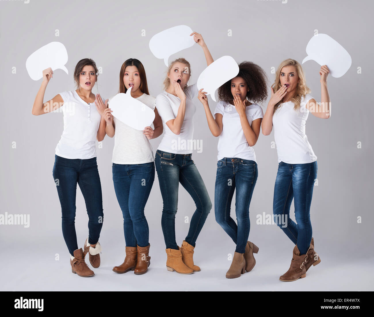 Shocked girls holding empty speech bubbles above heads. Debica, Poland - Stock Image