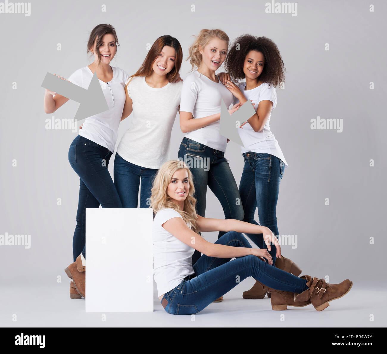 Multi-ethnic women displaying white board. Debica, Poland - Stock Image