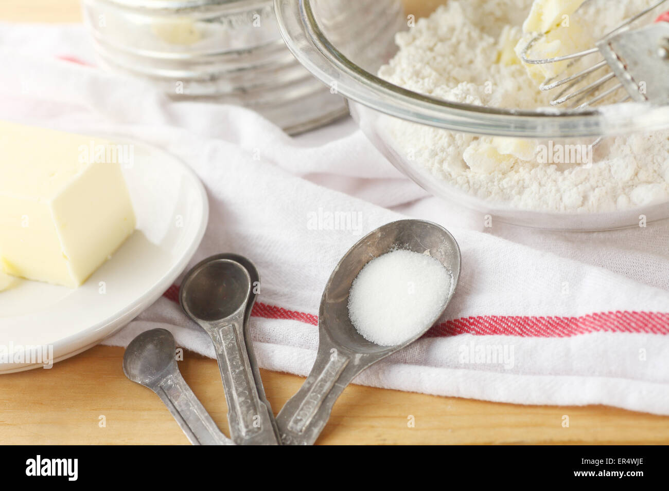 Mixing bowl with flour and butter, vintage sifter, measuring spoons and dish cloth - Stock Image