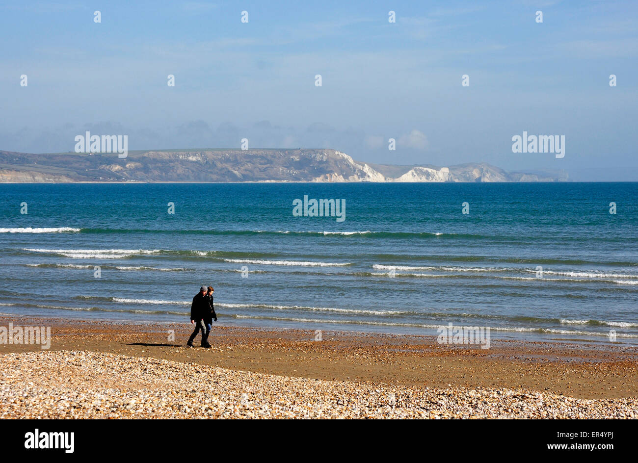 Dorset - Weymouth - couple walking on the beach - chalk cliffs backdrop across the bay - gentle waves lapping shore - Stock Image