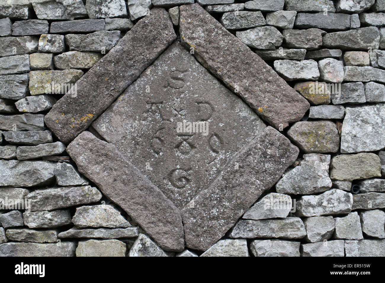 1689 date stone with an interesting history built into a wall near Wirksworth - Stock Image