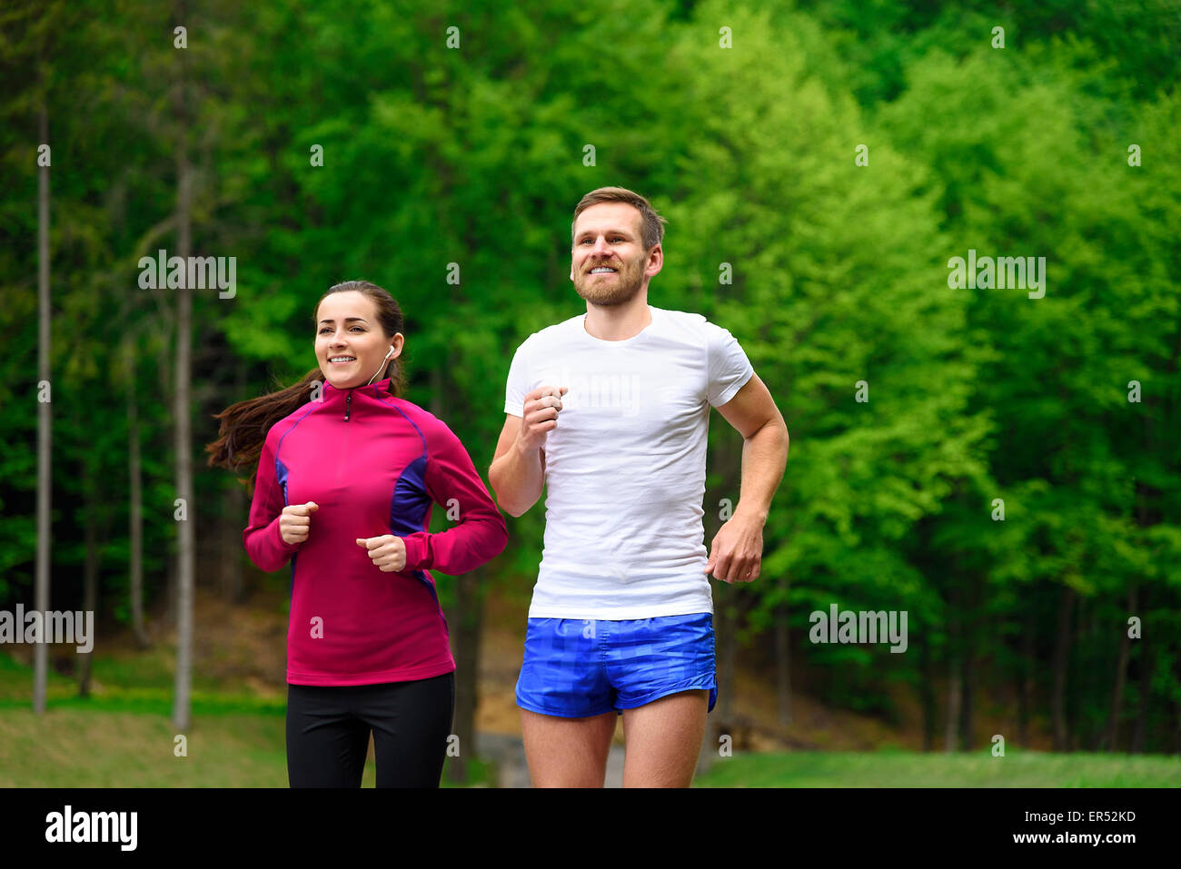 Couple running in park. - Stock Image