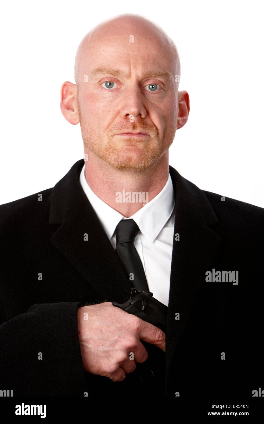bald headed armed and dangerous white man wearing heavy black overcoat pulling handgun out against a white studio - Stock Image