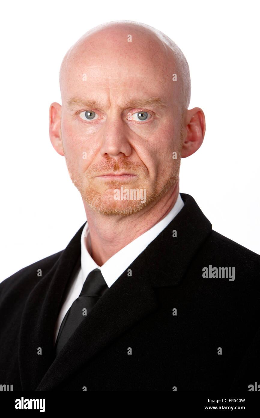 bald headed man wearing heavy black overcoat against a white studio background model released image - Stock Image