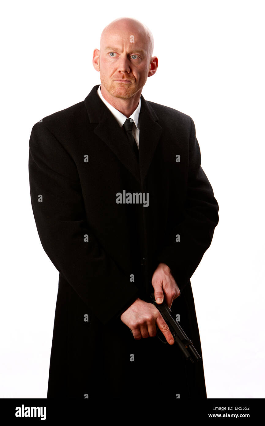 bald headed man wearing heavy black overcoat cocking automatic pistol against a white studio background model released - Stock Image