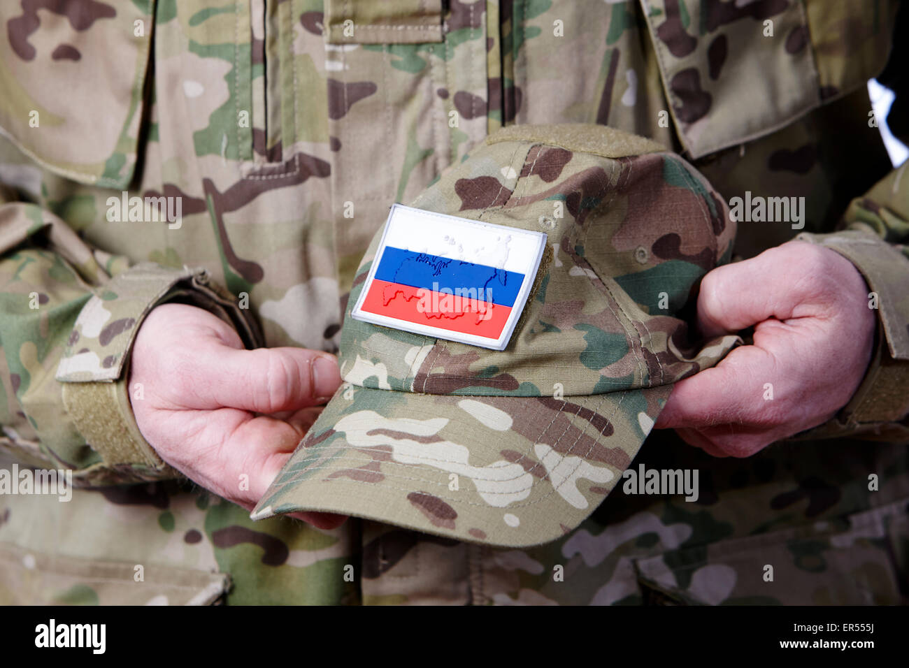 12c17141fb1 man in combat fatigues holding russian army camouflage hat - Stock Image