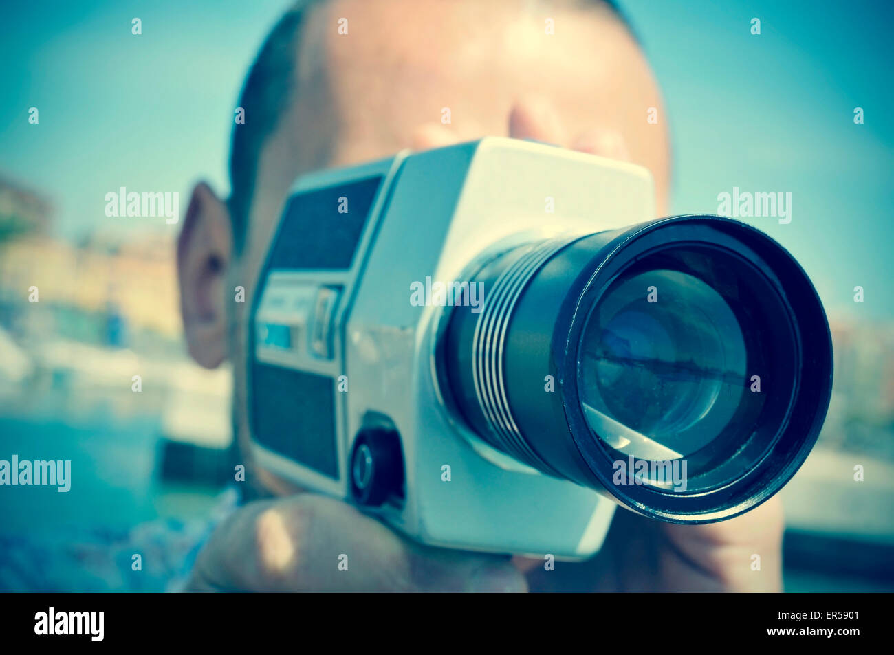 closeup of a young caucasian man filming with a retro film camera outdoors - Stock Image