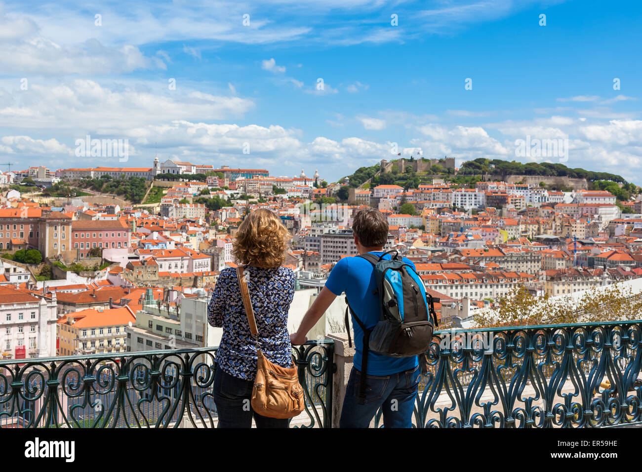 Tourist watching to Lisbon rooftop from Sao Pedro de Alcantara viewpoint - Miradouro in Portugal - Stock Image