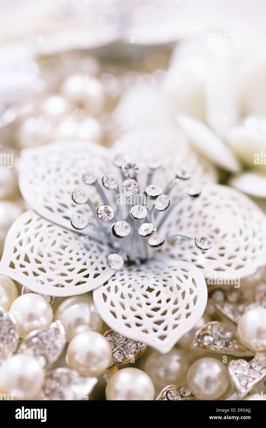 Close up of a white and silver metal jewelry flower lying on pearls and other jewels. - Stock Image