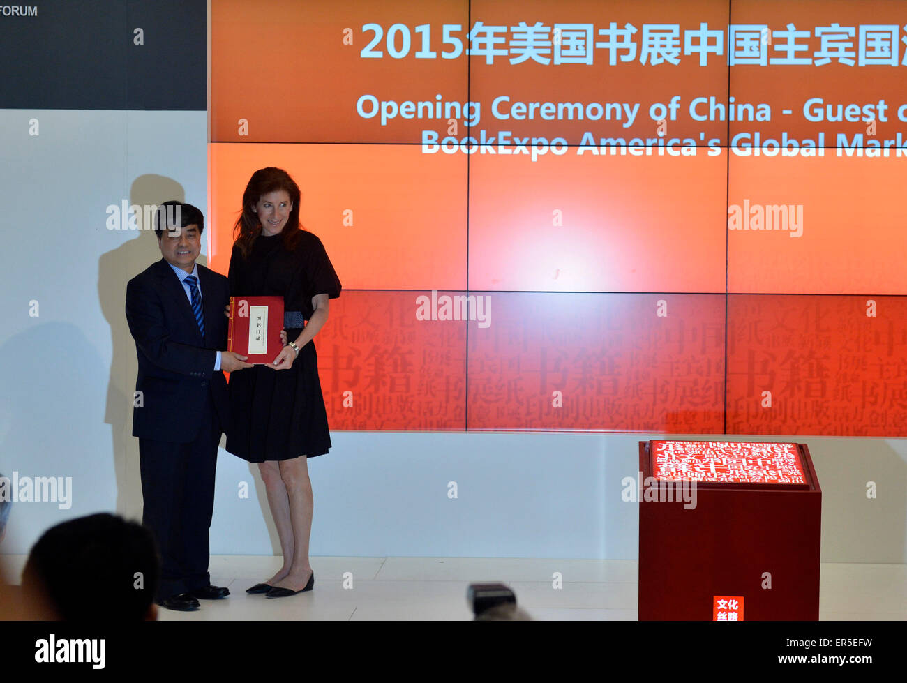 """(150527) -- NEW YORK, May 27, 2015 (Xinhua) -- Wu Shangzhi(L), vice minister of China's State Administration of Press, Publication, Radio, Film and Television, gives a book as gifts to Linda Johnson, the President & CEO of Brooklyn Public Library during the opening ceremony of China-Guest of Honor 2015 BookExpo America's Global Market Forum in New York, the United States, on May 27, 2015. Bringing in nearly 10,000 book titles from some 150 publishers, China came under the spotlight in this """"publishing and cultural capital of the world"""" as BookExpo America (BEA) 2015 kicked off in New York City Stock Photo"""