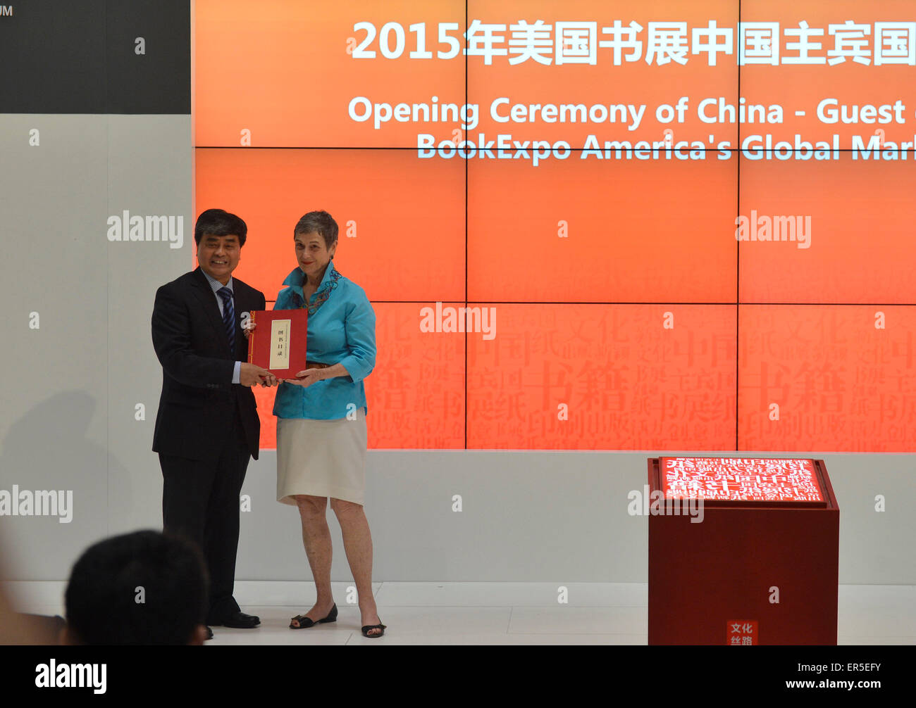 """(150527) -- NEW YORK, May 27, 2015 (Xinhua) -- Wu Shangzhi(L), vice minister of China's State Administration of Press, Publication, Radio, Film and Television, gives a book as gifts to Kristin Mc Daught, a representitive from New York Public Library during the opening ceremony of China-Guest of Honor 2015 BookExpo America's Global Market Forum in New York, the United States, on May 27, 2015. Bringing in nearly 10,000 book titles from some 150 publishers, China came under the spotlight in this """"publishing and cultural capital of the world"""" as BookExpo America (BEA) 2015 kicked off in New York C Stock Photo"""