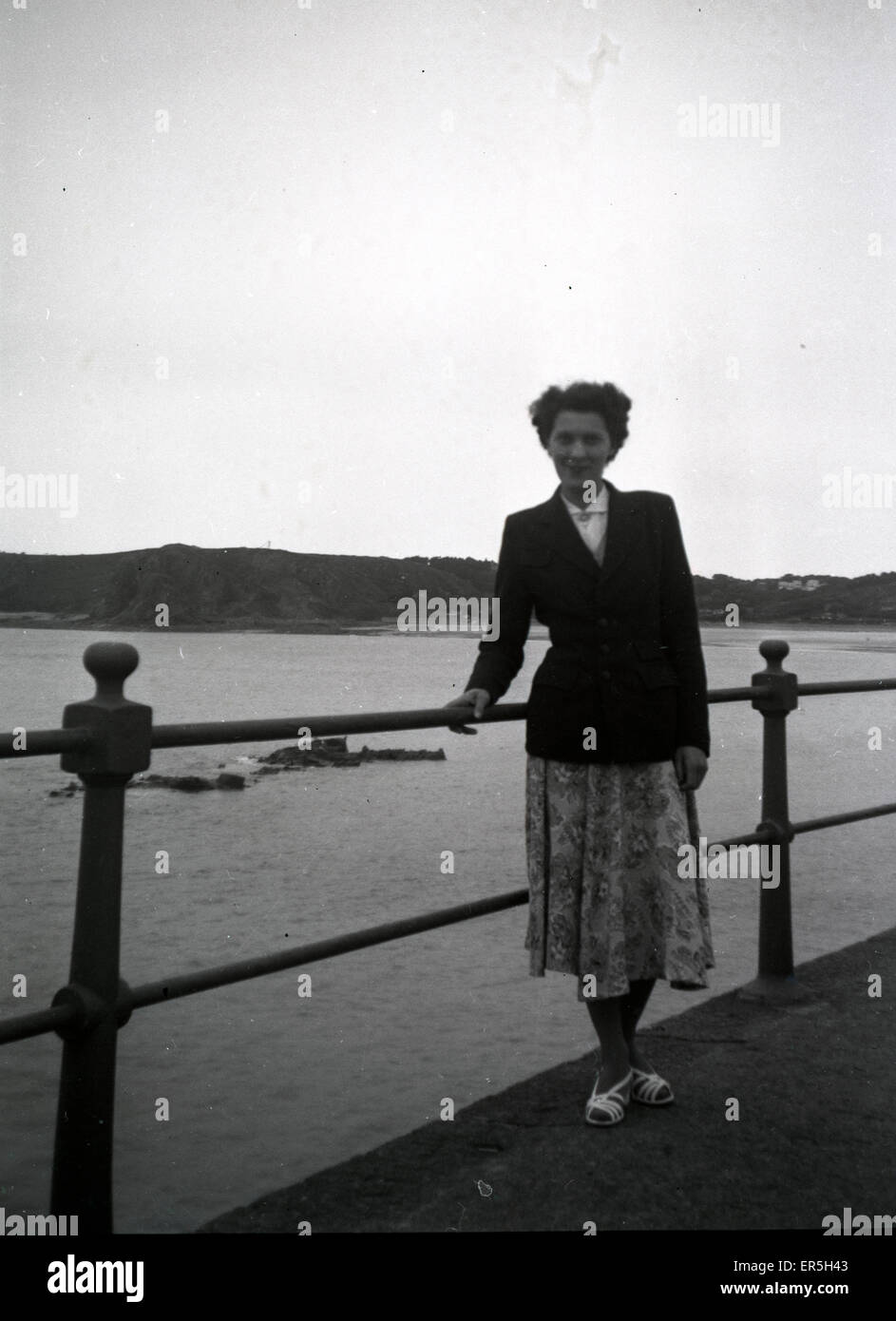 Holidaymaker by Railing, Unknown location, England.  1950s - Stock Image