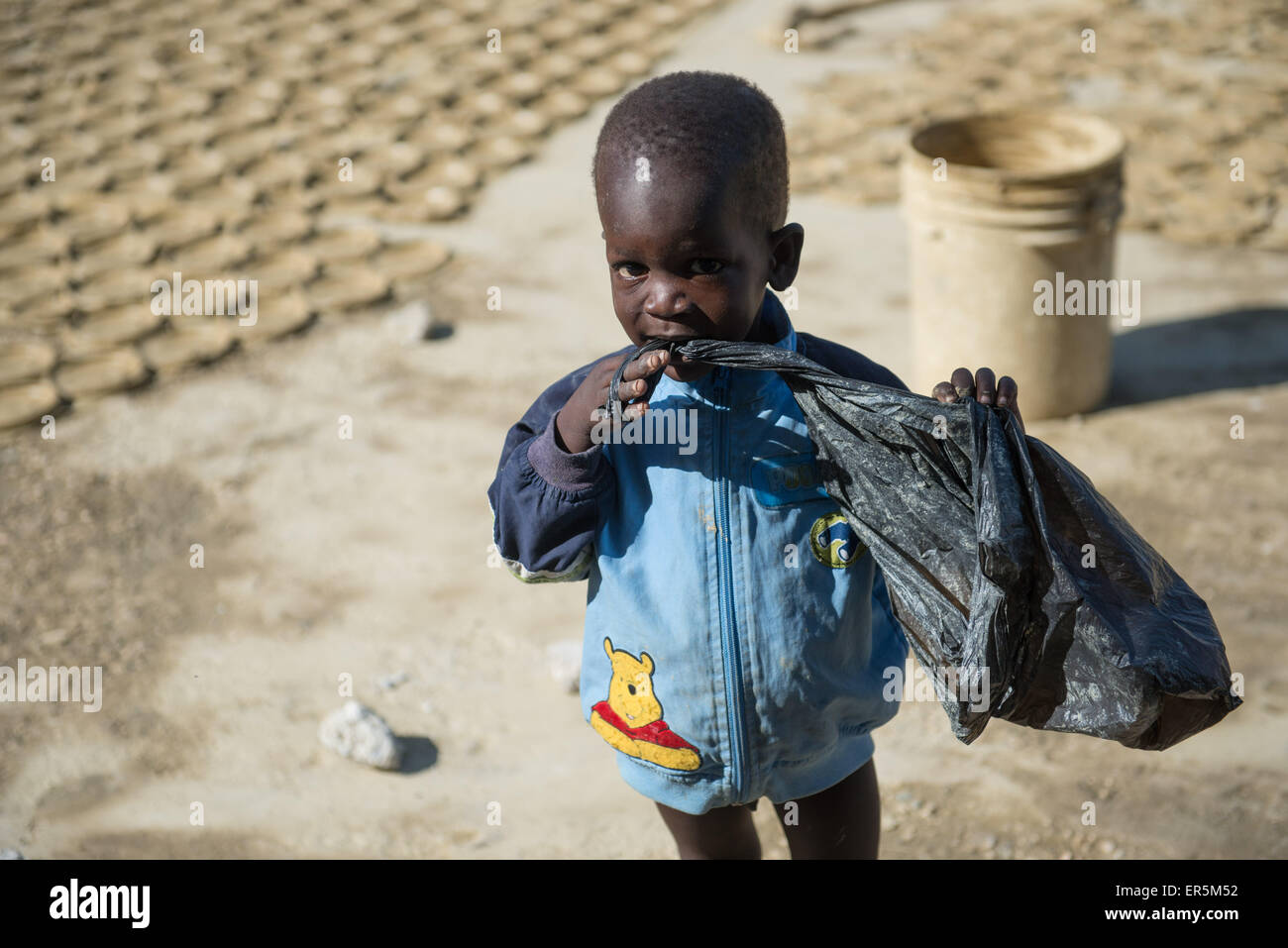 (150528) -- PORT AU PRINCE, May 28, 2015 (Xinhua) -- A boy bites a plastic bag in front of the mud cookies in the - Stock Image